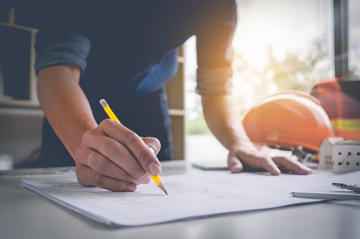 istock Architect man holding pencil working with laptop and blueprints for architectural plan, engineer sketching a construction project concept. 875088138