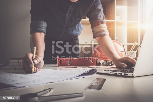 istock Architect man holding pencil working with laptop and blueprints for architectural plan, engineer sketching a construction project concept. 897853202