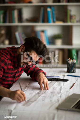 istock Architect man holding pencil working with laptop 1126666049