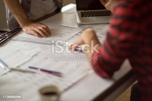 istock Architect man holding pencil working with laptop 1126666356