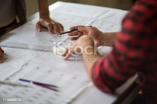 istock Architect man holding pencil working with laptop 1126666724