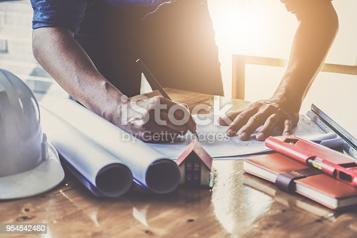 istock Architect man working with blueprints and holding house model for architectural plan,engineer sketching a construction project concept. 954542460