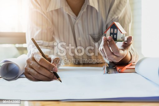 istock Architect man working with blueprints and holding house model for architectural plan,engineer sketching a construction project concept. 954543560