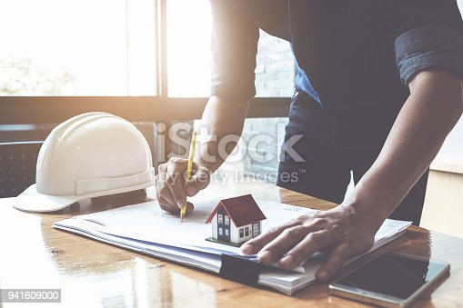 istock Architect man working with compasses and blueprints for architectural plan, engineer sketching a construction project concept. 941609000