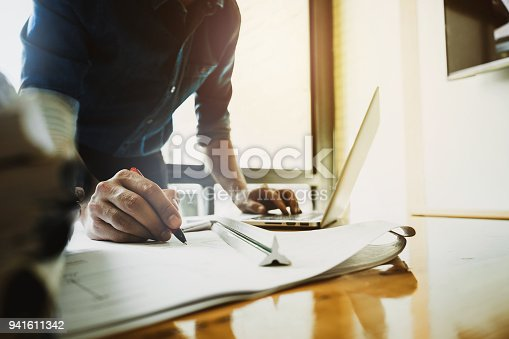 istock Architect man working with compasses and blueprints for architectural plan,engineer sketching a construction project concept. 941611342