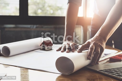 istock Architect man working with compasses and blueprints for architectural plan,engineer sketching a construction project concept. 956240766