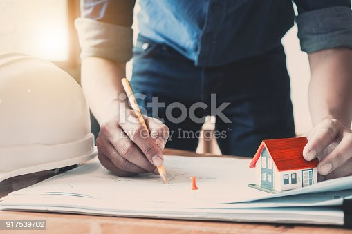 istock Architect man working with house model and blueprints for architectural plan, engineer sketching a construction project concept. 917539702