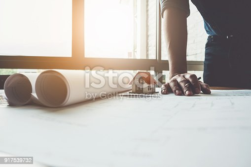 istock Architect man working with house model and blueprints for architectural plan, engineer sketching a construction project concept. 917539732
