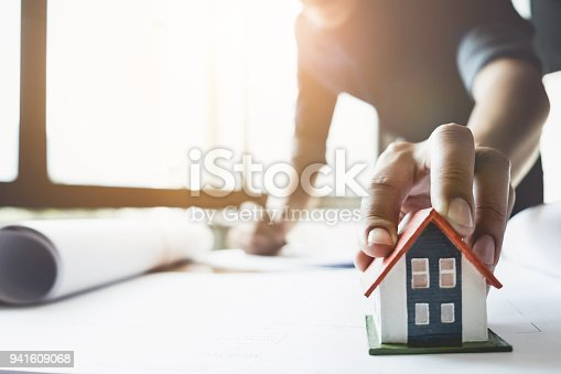 istock Architect man working with house model and blueprints for architectural plan, engineer sketching a construction project concept. 941609068