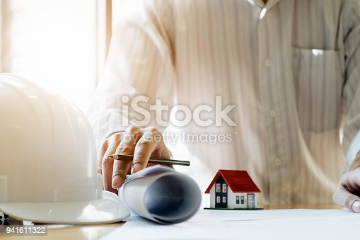 istock Architect man working with house model and blueprints for architectural plan, engineer sketching a construction project concept. 941611322