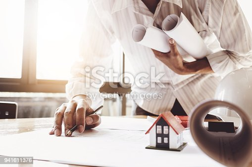 istock Architect man working with house model and blueprints for architectural plan, engineer sketching a construction project concept. 941611376