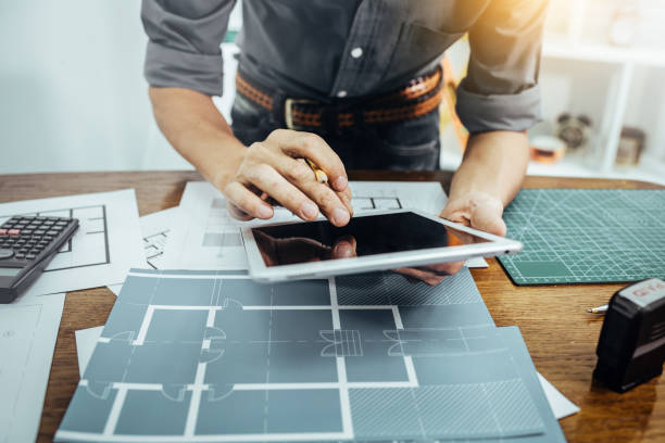 Architect man working with paper and blueprints for build new construction architectural plan sketching concept. stock photo