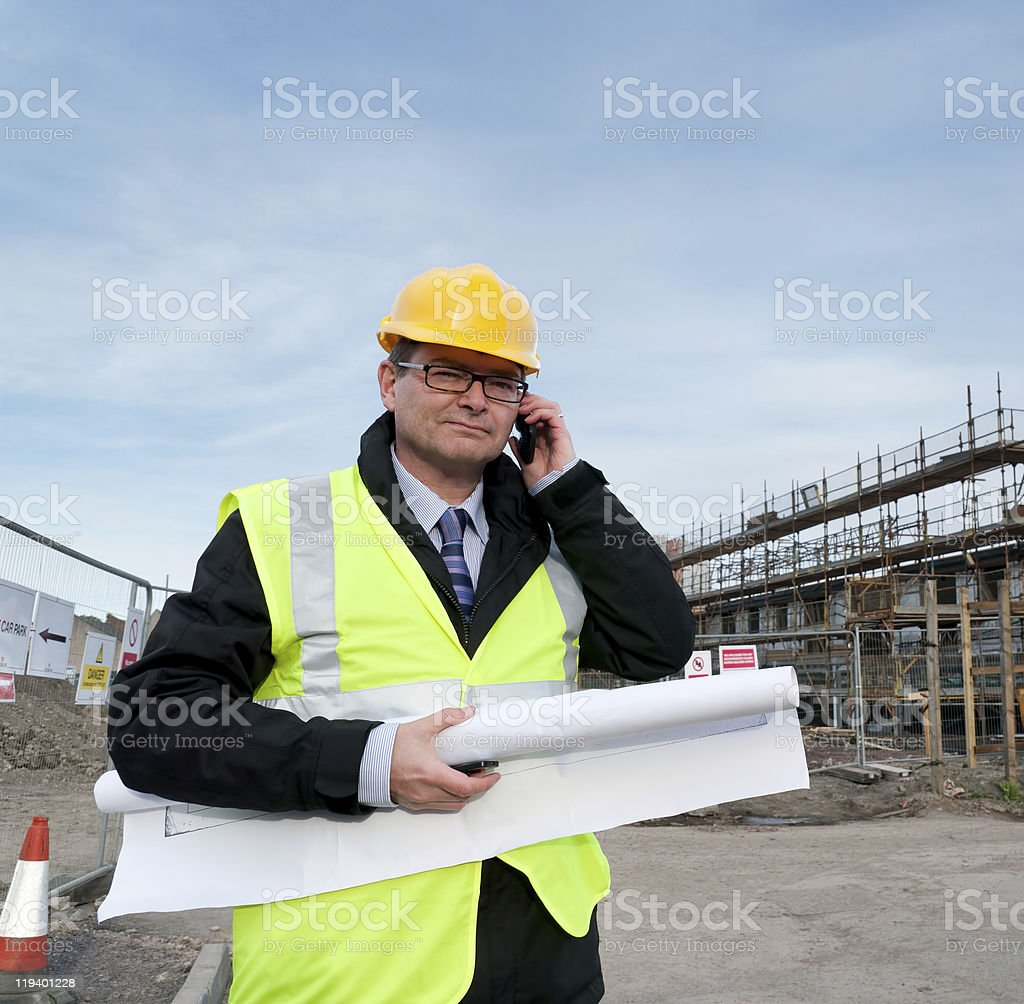 Architect on building site phoning royalty-free stock photo
