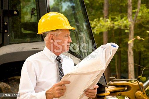 istock Architect on the jobsite.  Buldozer, heavy equipment in background. Blueprints. 170617772