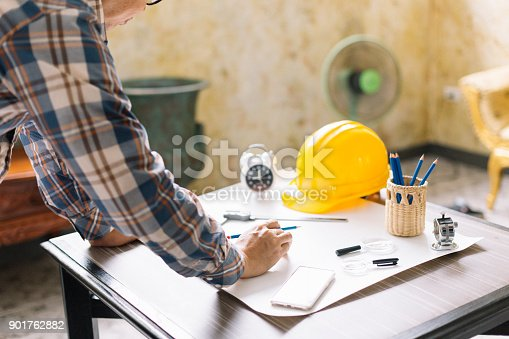 istock Architect or Construction Engineer sketching a construction project on drawing table with engineering tool in office. Construction engineering.Selective focus. 901762882