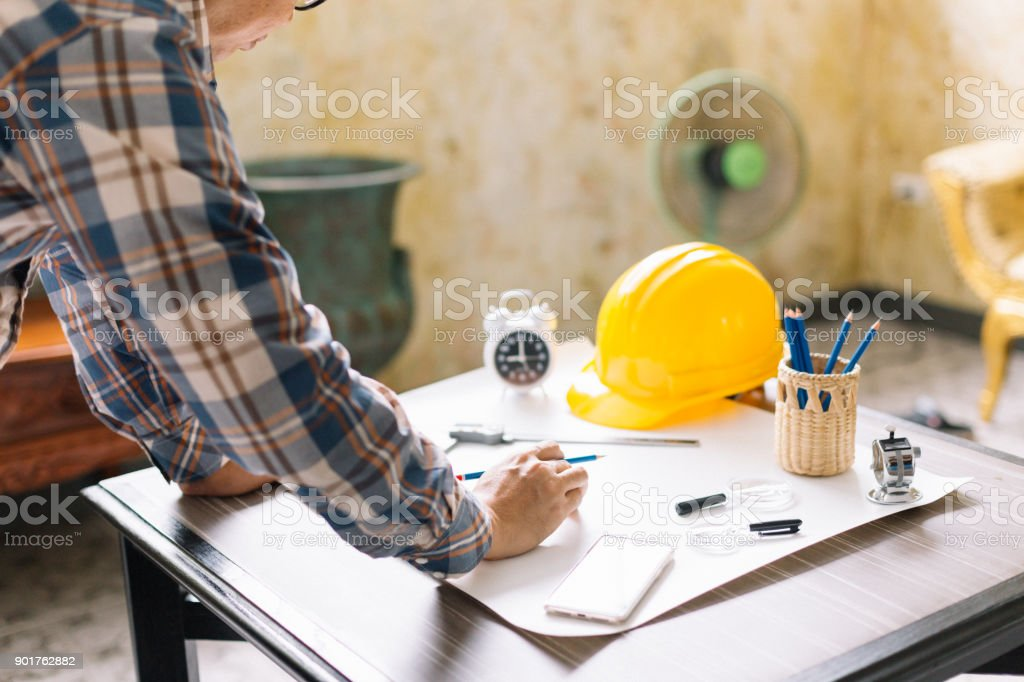 Architect or Construction Engineer sketching a construction project on drawing table with engineering tool in office. Construction engineering.Selective focus. stock photo