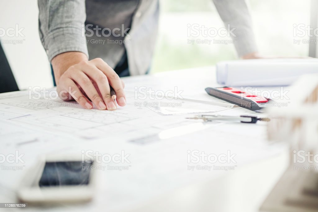 Architect or engineer working in office on blueprint. Architects...