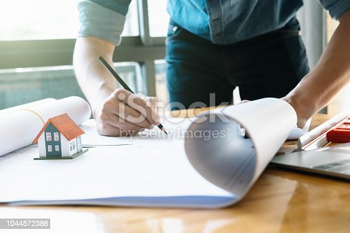 istock Architect or engineer working in office with blueprints,engineer inspection in workplace for architectural plan,sketching a construction project ,selective focus,Business construction concept. 1044572386