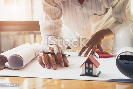832105172 istock photo Architect or engineer working in office with blueprints,engineer inspection in workplace for architectural plan,sketching a construction project ,selective focus,Business construction concept. 1182914314