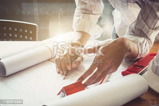 832105172 istock photo Architect or engineer working in office with blueprints,engineer inspection in workplace for architectural plan,sketching a construction project ,selective focus,Business construction concept. 1182914334