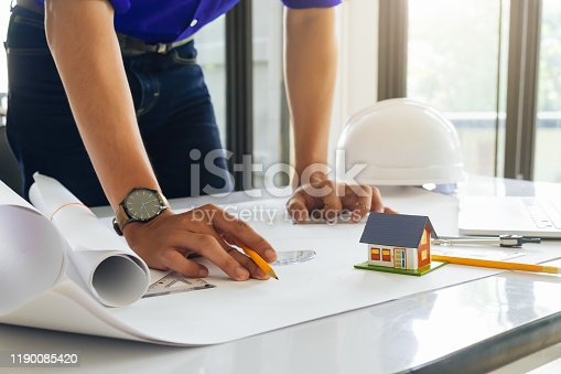 832105172 istock photo Architect or engineer working in office with blueprints,engineer inspection in workplace for architectural plan,sketching a construction project ,selective focus,Business construction concept. 1190085420