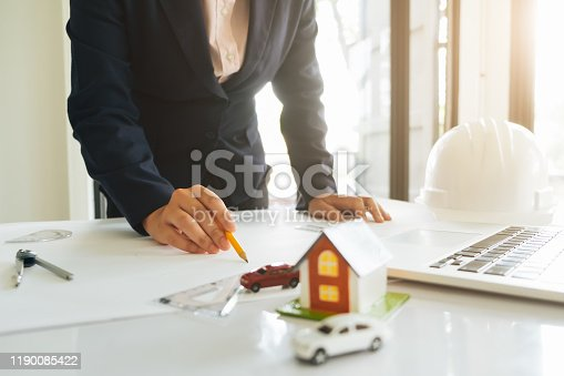 832105172 istock photo Architect or engineer working in office with blueprints,engineer inspection in workplace for architectural plan,sketching a construction project ,selective focus,Business construction concept. 1190085422