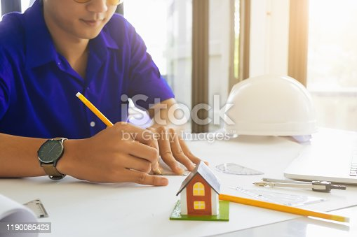 832105172 istock photo Architect or engineer working in office with blueprints,engineer inspection in workplace for architectural plan,sketching a construction project ,selective focus,Business construction concept. 1190085423