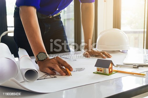 832105172 istock photo Architect or engineer working in office with blueprints,engineer inspection in workplace for architectural plan,sketching a construction project ,selective focus,Business construction concept. 1190085424