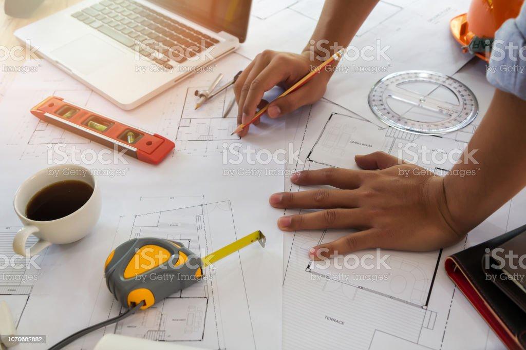 Architect or engineer working on blueprint in office, architectural...