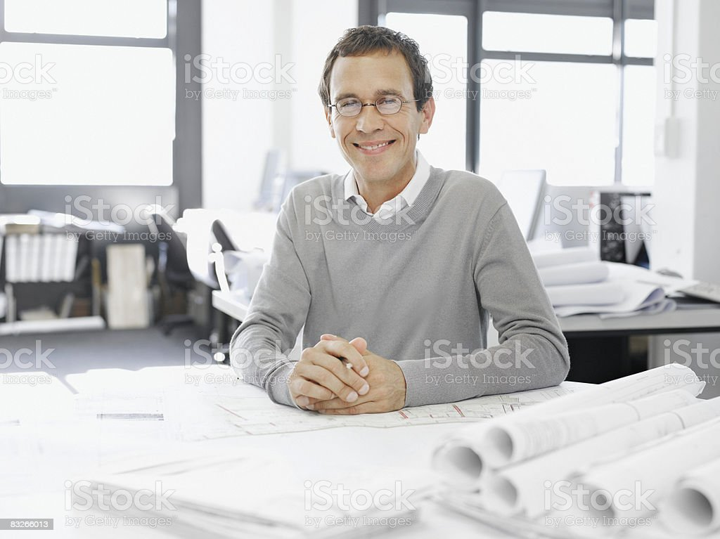 Architect posing with blueprints royalty free stockfoto