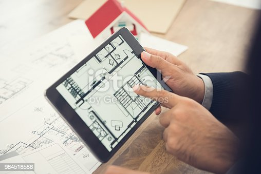 952643774 istock photo Architect presenting house floor plan to client on tablet computer 984518586