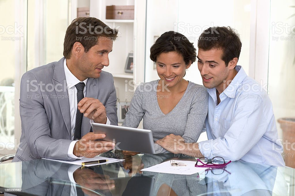 Architect presenting new project to a smiling young couple stock photo