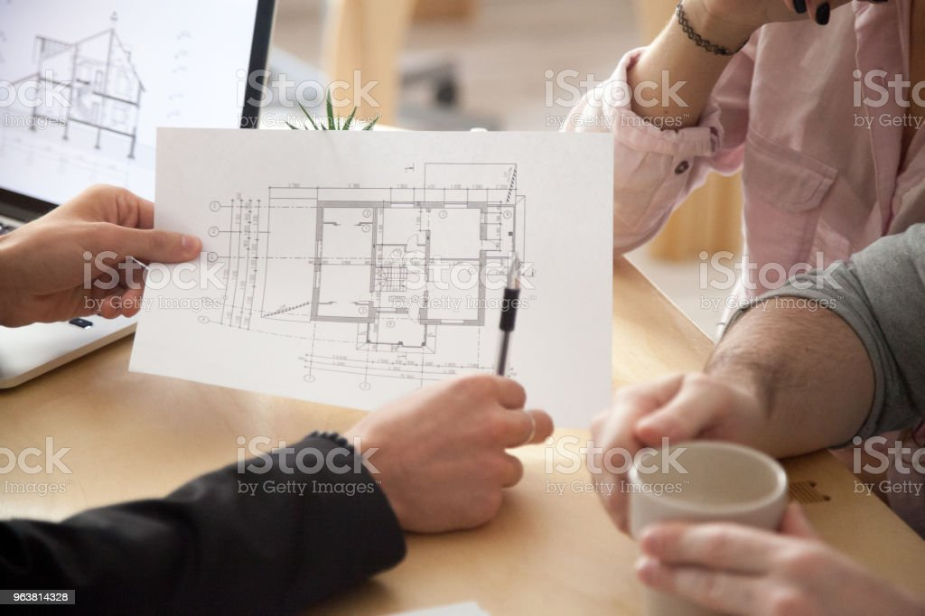 Architect, realtor or designer consulting couple with apartment plan, closeup stock photo