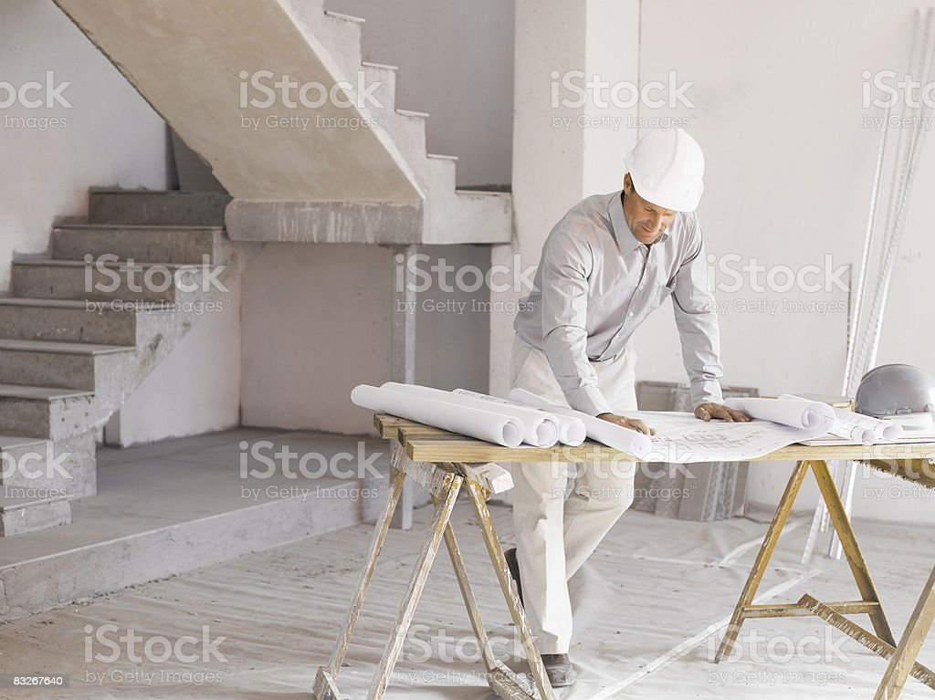 Architect reviewing blueprints at construction site stock photo