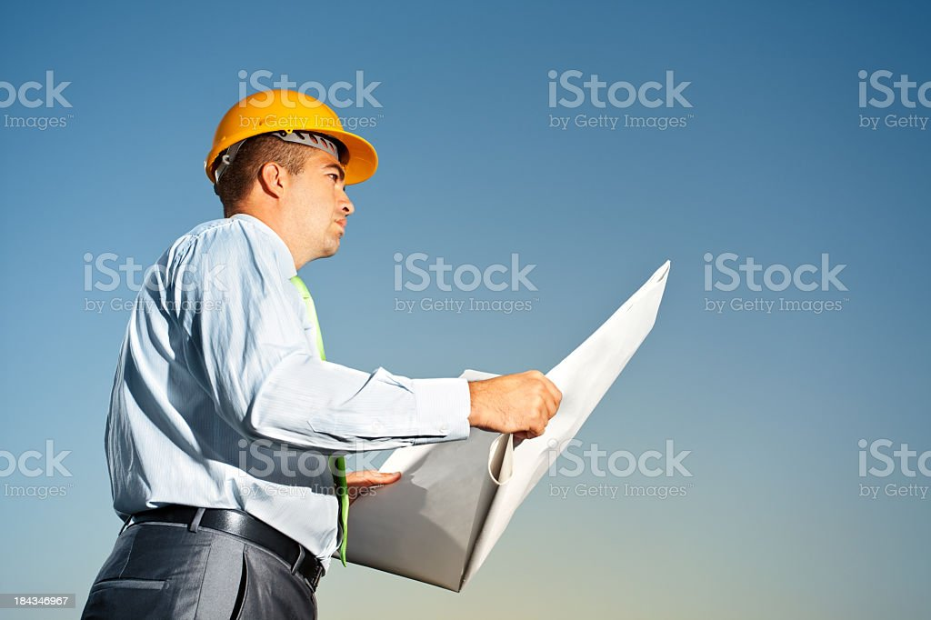 Architect Reviews Plans At A Construction Site royalty-free stock photo