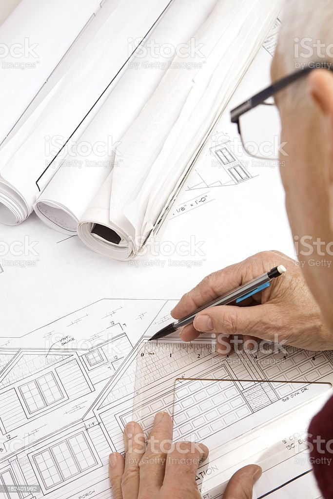 Architect Revising Blueprint Lines with a Triangle and Pencil royalty-free stock photo