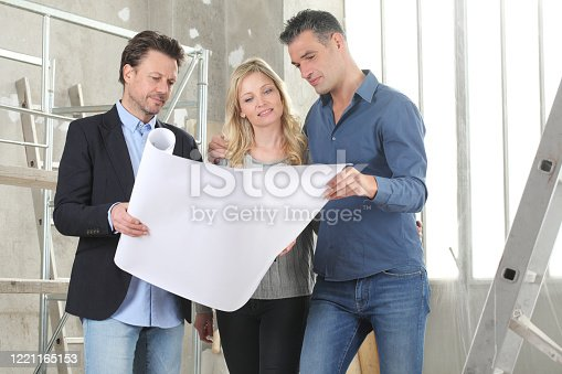 1040654052 istock photo Architect showing house design plans to a young couple. House building goal concept. Meeting at interior construction site to talk about house appearance, interior decoration and home layout 1221165153