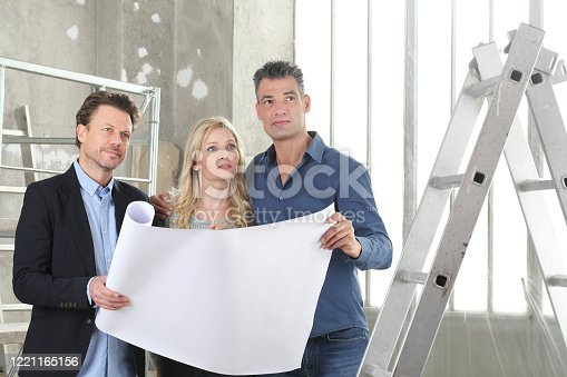 1040654052 istock photo Architect showing house design plans to a young couple. House building goal concept. Meeting at interior construction site to talk about house appearance, interior decoration and home layout 1221165156