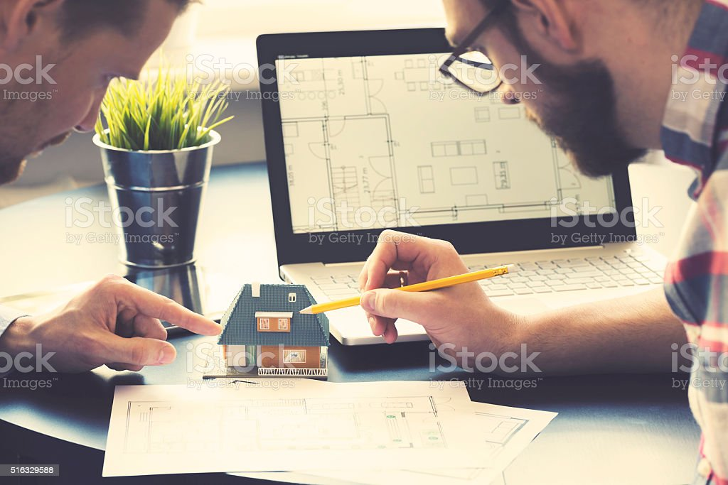 architect showing new family house model to customer at office stock photo