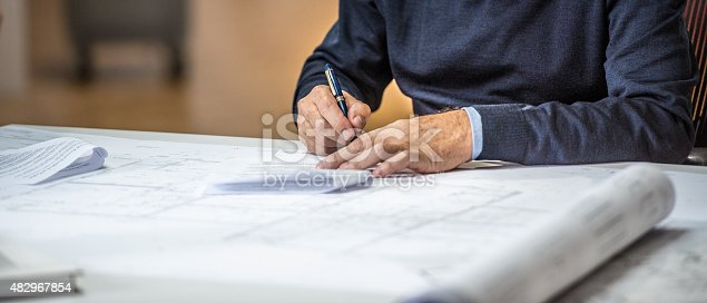Architect signing papers at his desk. Panoramic shot of hands and table, head not visible.