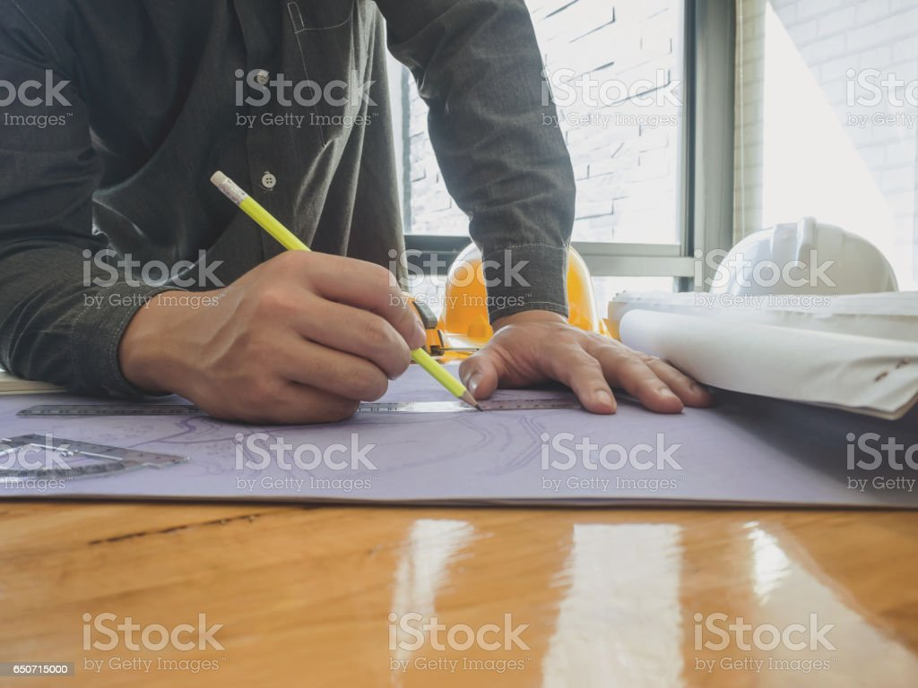 Architect sketching a construction project blueprint architectural architect sketching a construction project blueprint architectural concept royalty free stock photo malvernweather Gallery