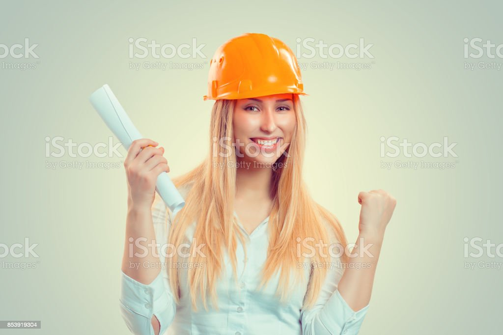 Architect successful. Closeup portrait happy smiling young construction woman yellow cap thumbs arm fist up celebrating win isolated green background. Positive human emotion facial expression attitude stock photo