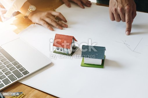 istock Architect Team Brainstorming Planning Design, Civil engineer sketching a blueprint of construction project with small house model and safety helmet in office, Construction Concept. 986270818