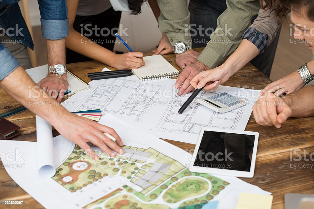 Architect team discussing on blueprints stock photo