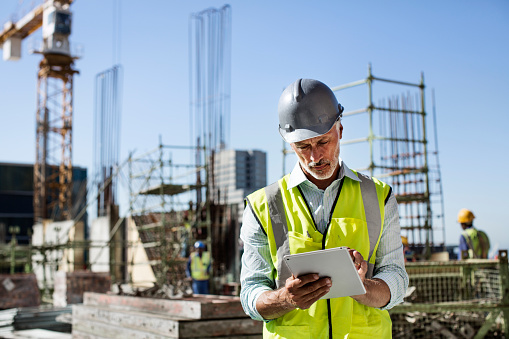 Male architect using digital tablet at construction site against clear sky