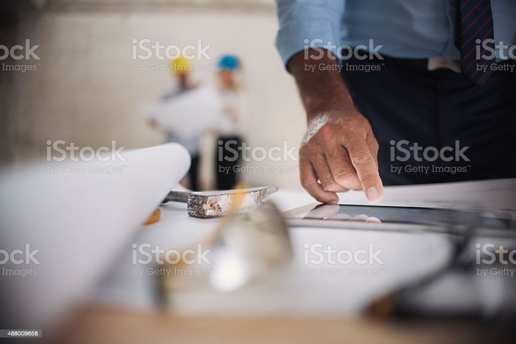 Architect using digital tablet to check plans on construction site stock photo