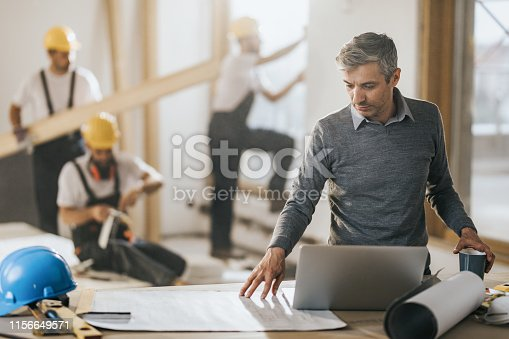 891274328 istock photo Architect using going through housing plans at construction site. 1156649571