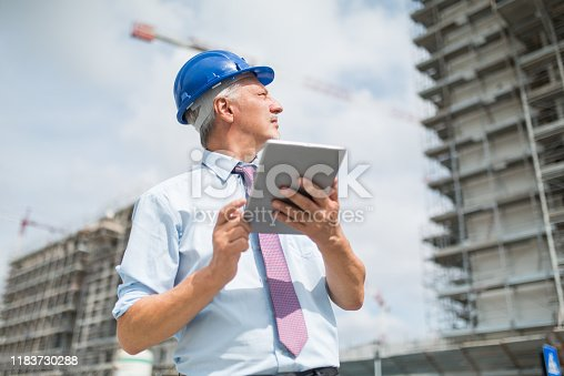 istock Architect using his tablet in front of a construction site 1183730288