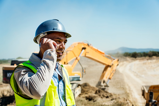Male architect using mobile phone with bulldozer in background at quarry