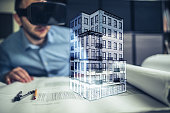 Male Architect wearing augmented reality headsets looking at the virtual model of his project